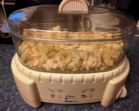 3 cups of cauliflower florets, and two cloves of garlic, ready to steam for 12 minutes